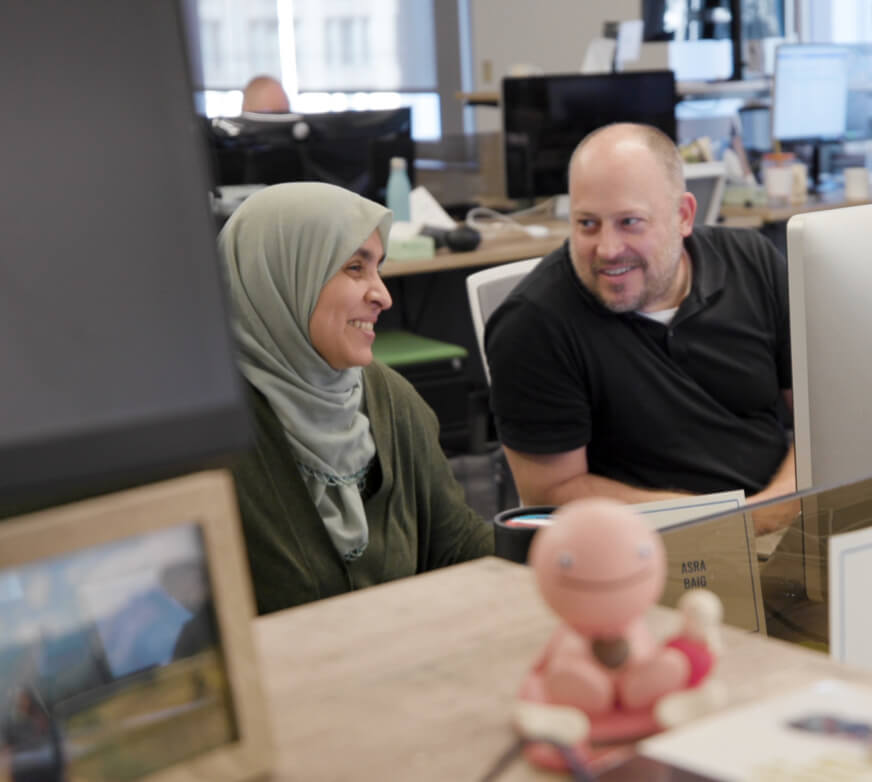 A man and a woman smiling and collaborating in an office setting